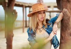 Όμορφη γυναίκα στο άγριο δυτικό ύφος κάουμποϋ, το καπέλο κάουμποϋ και το σακάκι τζιν, photosession πορτρέτου μόδας Στοκ φωτογραφία με δικαίωμα ελεύθερης χρήσης
