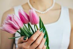 Όμορφη γυναίκα στο άσπρο περιδέραιο φορεμάτων και μαργαριταριών που κρατά ένα ροζ Στοκ Εικόνες