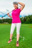 Όμορφη γυναίκα στο γήπεδο του γκολφ που κοιτάζει πίσω από την πετώντας σφαίρα Στοκ εικόνα με δικαίωμα ελεύθερης χρήσης