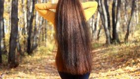 Όμορφη γυναίκα στο δάσος με την πολύ μακριά χρυσή τρίχα στην ηλιόλουστη ημέρα φθινοπώρου απόθεμα βίντεο