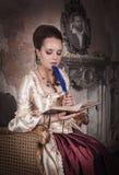 Όμορφη γυναίκα στο ιστορικό μεσαιωνικό φόρεμα με το ημερολόγιο Στοκ Εικόνες