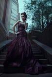 Όμορφη γυναίκα στο ιώδες φόρεμα στοκ εικόνες