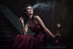 Όμορφη γυναίκα στο ιώδες φόρεμα στοκ εικόνα