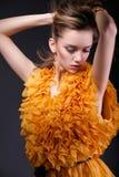 Όμορφη γυναίκα στο κίτρινο φόρεμα που κοιτάζει κάτω Στοκ εικόνα με δικαίωμα ελεύθερης χρήσης