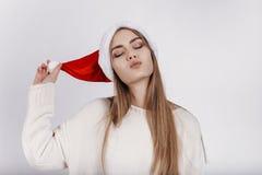 Όμορφη γυναίκα στο καπέλο santa που προσπαθεί να σας φιλήσει Στοκ Εικόνες