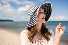 Όμορφη γυναίκα στο καπέλο που στέκεται στο γέλιο παραλιών Στοκ φωτογραφίες με δικαίωμα ελεύθερης χρήσης