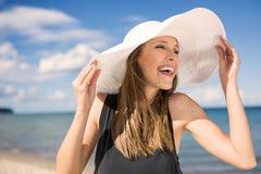 Όμορφη γυναίκα στο καπέλο στην παραλία που γελά και που κοιτάζει μακριά Στοκ φωτογραφία με δικαίωμα ελεύθερης χρήσης