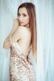 Όμορφη γυναίκα στο κομψό ακριβό λαμπρό χρυσό φόρεμα βραδιού με το γυμνό οπίσθιο τμήμα με τη σκοτεινή σύνθεση και τα μαργαριτάρια  Στοκ φωτογραφία με δικαίωμα ελεύθερης χρήσης