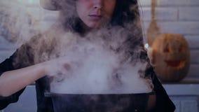 Όμορφη γυναίκα στο κοστούμι μαγισσών που κατασκευάζει τη μαγική φίλτρο, που προετοιμάζεται για αποκριές απόθεμα βίντεο