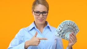 Όμορφη γυναίκα στο κοστούμι που δείχνει το δάχτυλο στη δέσμη των δολαρίων, κερδοφόρα επιχείρηση απόθεμα βίντεο