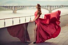 Όμορφη γυναίκα στο κόκκινο κυματίζοντας φόρεμα ανασκόπηση αστική Στοκ Εικόνες