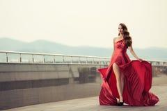 Όμορφη γυναίκα στο κόκκινο κυματίζοντας φόρεμα ανασκόπηση αστική Στοκ φωτογραφίες με δικαίωμα ελεύθερης χρήσης