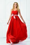 Όμορφη γυναίκα στο κόκκινο μακρύ φόρεμα. στοκ φωτογραφίες