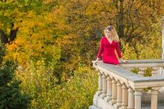 Όμορφη γυναίκα στο κόκκινο φόρεμα και ηλικιωμένο arhitecture στο υπόβαθρο φύσης πτώσης Στοκ εικόνες με δικαίωμα ελεύθερης χρήσης