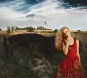 Όμορφη γυναίκα στο κόκκινο φόρεμα μπροστά από το μαύρο άλογο Στοκ Εικόνες