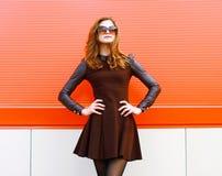 Όμορφη γυναίκα στο μαύρο φόρεμα και γυαλιά ηλίου που θέτουν υπαίθρια στοκ φωτογραφία