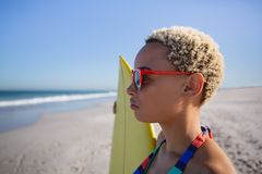 Όμορφη γυναίκα στο μπικίνι και γυαλιά ηλίου που στέκονται με την ιστιοσανίδα στην παραλία στην ηλιοφάνεια στοκ φωτογραφία