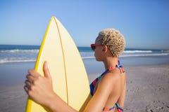 Όμορφη γυναίκα στο μπικίνι και γυαλιά ηλίου που στέκονται με την ιστιοσανίδα στην παραλία στην ηλιοφάνεια στοκ εικόνες με δικαίωμα ελεύθερης χρήσης