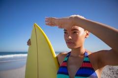 Όμορφη γυναίκα στο μπικίνι με τα μάτια προστατευτικών καλυμμάτων ιστιοσανίδων στην παραλία στην ηλιοφάνεια στοκ εικόνες