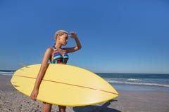 Όμορφη γυναίκα στο μπικίνι με τα μάτια προστατευτικών καλυμμάτων ιστιοσανίδων στην παραλία στην ηλιοφάνεια στοκ εικόνα με δικαίωμα ελεύθερης χρήσης