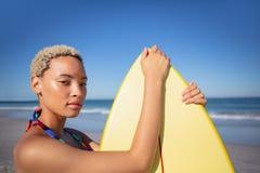 Όμορφη γυναίκα στο μπικίνι που στέκεται με την ιστιοσανίδα στην παραλία στην ηλιοφάνεια στοκ εικόνες με δικαίωμα ελεύθερης χρήσης