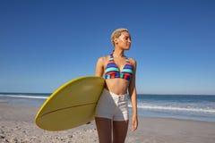 Όμορφη γυναίκα στο μπικίνι που στέκεται με την ιστιοσανίδα στην παραλία στην ηλιοφάνεια στοκ φωτογραφία με δικαίωμα ελεύθερης χρήσης