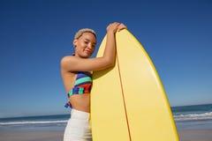 Όμορφη γυναίκα στο μπικίνι που στέκεται με την ιστιοσανίδα στην παραλία στην ηλιοφάνεια στοκ εικόνα με δικαίωμα ελεύθερης χρήσης