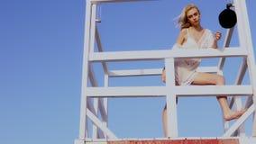 Όμορφη γυναίκα στο μπικίνι που στέκεται στο σταθμό lifeguard, lifeguard πύργος απόθεμα βίντεο