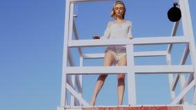 Όμορφη γυναίκα στο μπικίνι που στέκεται στο σταθμό lifeguard, lifeguard πύργος φιλμ μικρού μήκους