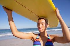 Όμορφη γυναίκα στο μπικίνι που φέρνει την ιστιοσανίδα στο κεφάλι της στην παραλία στην ηλιοφάνεια στοκ εικόνα με δικαίωμα ελεύθερης χρήσης