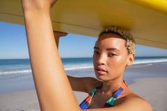 Όμορφη γυναίκα στο μπικίνι που φέρνει την ιστιοσανίδα στο κεφάλι της στην παραλία στην ηλιοφάνεια στοκ εικόνες με δικαίωμα ελεύθερης χρήσης