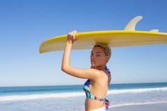 Όμορφη γυναίκα στο μπικίνι που φέρνει την ιστιοσανίδα στο κεφάλι της στην παραλία στην ηλιοφάνεια στοκ εικόνες