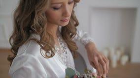 Όμορφη γυναίκα στο μπουρνούζι που εξετάζει τη γαμήλια ανθοδέσμη φιλμ μικρού μήκους