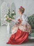 Όμορφη γυναίκα στο ντεμοντέ μεσαιωνικό φόρεμα στον καναπέ Στοκ φωτογραφίες με δικαίωμα ελεύθερης χρήσης