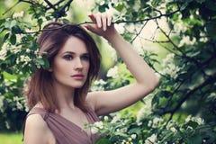 Όμορφη γυναίκα στο λουλούδι δέντρων της Apple Στοκ Φωτογραφίες