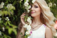 Όμορφη γυναίκα στο πάρκο κοντά στα ανθίζοντας τριαντάφυλλα του Μπους στοκ φωτογραφία