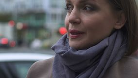 Όμορφη γυναίκα στο παλτό και μαντίλι που αισθάνεται το κρύο εξωτερικό, την τάση και τη μοντέρνη εξάρτηση απόθεμα βίντεο