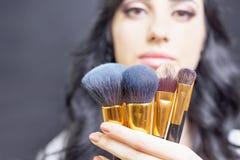 Όμορφη γυναίκα στο σαλόνι ομορφιάς με το σύνολο βουρτσών makeup Στοκ Φωτογραφίες