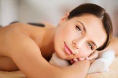 Όμορφη γυναίκα στο σαλόνι SPA με τις καυτές πέτρες Στοκ Εικόνα