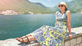 Όμορφη γυναίκα στο φόρεμα και καπέλο στην ακτή του νησιού Boka Kotorska Μαυροβούνιο Στοκ Εικόνες