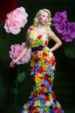 Όμορφη γυναίκα στο φόρεμα των λουλουδιών στο υπόβαθρο των μεγάλων λουλουδιών Στοκ Εικόνες