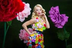 Όμορφη γυναίκα στο φόρεμα των λουλουδιών στο υπόβαθρο των μεγάλων λουλουδιών Στοκ Εικόνα