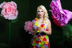 Όμορφη γυναίκα στο φόρεμα των λουλουδιών στο υπόβαθρο των μεγάλων λουλουδιών Στοκ εικόνες με δικαίωμα ελεύθερης χρήσης