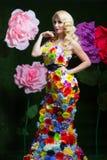 Όμορφη γυναίκα στο φόρεμα των λουλουδιών στο υπόβαθρο των μεγάλων λουλουδιών Στοκ Φωτογραφίες