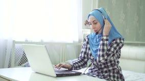 Όμορφη γυναίκα στο hijab στον υπολογιστή με την κάσκα, απόμακρη εργασία, τηλεφωνικό κέντρο απόθεμα βίντεο