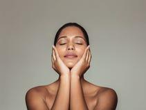 Όμορφη γυναίκα σχετικά με το φρέσκο καθαρό πρόσωπό της στοκ φωτογραφία