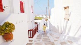 Όμορφη γυναίκα υπαίθρια στις παλαιές οδούς μια Μύκονος Κορίτσι στην οδό του χαρακτηριστικού ελληνικού παραδοσιακού χωριού με τους φιλμ μικρού μήκους