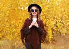 Όμορφη γυναίκα φθινοπώρου μόδας με το φλυτζάνι καφέ που φορά τα γυαλιά ηλίου μαύρων καπέλων και πλεκτό poncho πέρα από τα κίτρινα Στοκ Φωτογραφίες