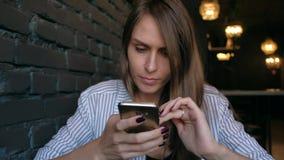 Όμορφη γυναίκα χρησιμοποιώντας το smartphone και πίνοντας τον καφέ στον καφέ απόθεμα βίντεο