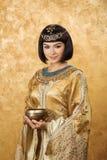 Όμορφη γυναίκα όπως την αιγυπτιακή βασίλισσα Κλεοπάτρα με το φλυτζάνι στο χρυσό υπόβαθρο Στοκ Εικόνες
